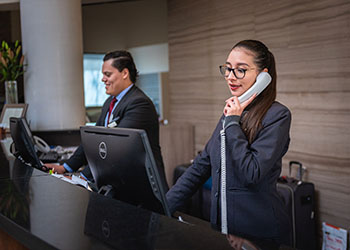 Hotel Front Desk Reception Staff Talk To Customers Over the Phone and in Person