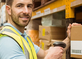 Man Scans Barcode Label in Warehouse