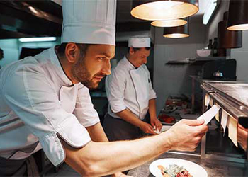 Restaurant Chef Looks at Food Order Ticket